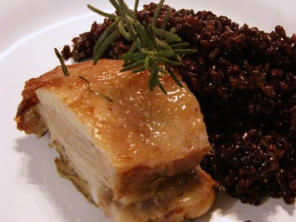 foto de um prato com um pedaço de uma costela suína assada arroz negro japonico e um ramo de alecrim para decorar