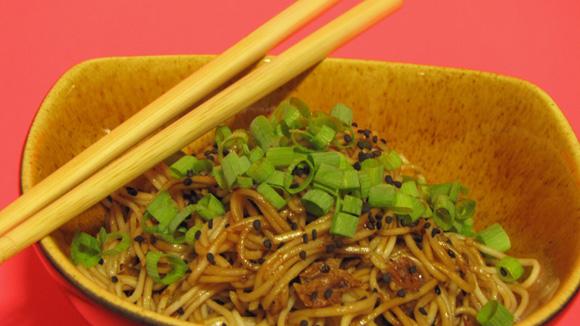 foto de um bowl com macarrao somen gergelim preto sardinha e shoyo com os hashis apoiados sobre o bowl