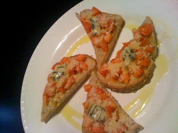 foto de um prato com 4 bruschetas de tomate, parmesão e gorgonzola