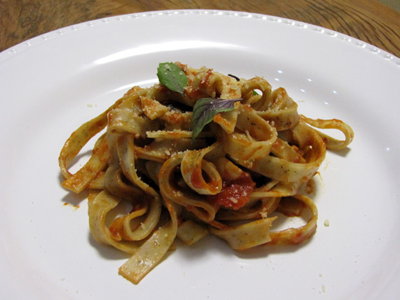 foto de um prato com fetuccine de manjericão e molho de azeitona e folhas de manjericão fresco