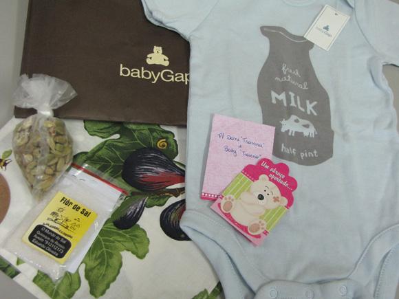 foto de um macacão de bebê, um saquinho com sementes de cardamomo, um saquinho de flor de sal e um pano de mão com desenhos de figos